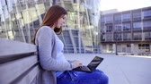 быстро : Attractive woman sit on bench and work on laptop in front of futuristic glass building with no person around..Female student with laptop on legs in front of school 4K Стоковые видеозаписи