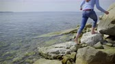 inclinar : Walk on sea rocks and lean to sunbath 4K. Woman in blue sweater and jeans tries temperature of water and walks on rocks barefoot to sunbath leaning on huge rock. Stock Footage