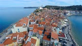 city : Flying over old buildings surrounded with sea 4K. Aerial flying over old traditional buildings at sea coast on a sunny day. View on roofs, sea on both side and blue sky.