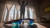 light : Lifting up wind kite in mystical room 4K. Low wide angle with teenager kid holding wind kite on two strings, swinging in a room with bright windows in background. Slow motion.