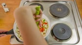crane : Above electric stove cooking meat with vegetables. Person mixing vegetables chicken meat with pieces of vegetables with help of green plastic spoon. Stock Footage