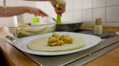 burrito : Preparing tortilla with sauce and putting in baking tray. Person preparing traditional Mexican dish from tortilla with meat and vegetables inside. Rolling together and putting in baking tray crane shot.