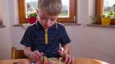 painting : Zooming on kid painting egg on table 4K. Medium slow motion shot of young child in kitchen with bright windows in background coloring eggs with edible colors. Dressed in blue shirt. Stock Footage
