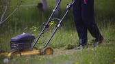 Lifting and pushing lawnmower to cut grass close up . Person trimming green grass with yellow motorized lawnmower. Pushing in wrong direction.