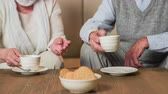 severler : Grandparents with tea cups in hands . Two old person in retro clothes with tea cups and cookies on table sit on sofa. Close up on tea cups.
