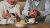 взял : Elderly person holding a TV remote controller . Old couple sit on sofa and husband trying to operate a TV remote, grandma take it from hand and put on table. Close up slow motion.