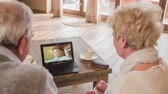 Grandparents thumbs up to grandson over video call . Two elderly person using new technology live video call with laptop computer and talking to grandson over-sea about football achievements. Over shoulder view.