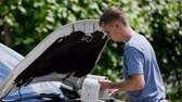 Finding a solution in car manual looking under the hood. Young attractive man holding instructions manual for fixing car problems. Standing beside the opened car hood looking in to engine parts. Stock Footage