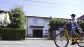 Driving yellow bicycle and throwing newspaper . Side view driving beside a boy postman delivering newspaper to people on a sunny day.