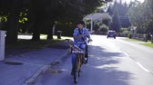 Boy mailman on bicycle throwing newspaper . Camera driving in front of kid on bicycle delivering newspaper rolls full of bicycle cart. Sun shining from behind. Houses on both side.