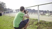 Photographer on harness race shooting competitors . Behind the back of young photographer with professional camera making photos of competition and the start of harness race. Sunny day. Stock Footage