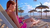 Woman read book on sand beach at sea. Behind the back view of woman on lounger lying and reading a book. Beach straw umbrellas and sea with blue sky in background.
