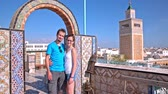 Couple posing with Tunis town in background. Medium shot of man and woman standing under arc doors on balcony with view over Tunis medina and huge Minaret in the middle.