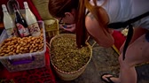 Woman smelling herbs from big basket. Top view of female person grabbing herbs in hands on marketplace.