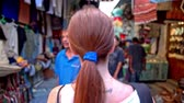 Tourist with backpack walk through Tunis. Female person with long brown hair and a tattoo on shoulder walking through street with shops on both sides.