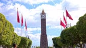 tunisian flag : Clock tower in Tunis. Wide shot low angle of clock tower in Tunis with six red flags of Tunisia wave in wind.