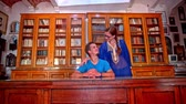Man in the retro cabinet visited by wife. Male person behind the desk in old wooden cabinet with many books in background, woman in traditional Sidi Bou Said dress stands beside husband.