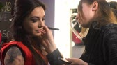 make up applying : Makeup artist makes makeup for woman model Stock Footage
