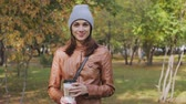 A young woman in a Park drinking coffee Vídeos