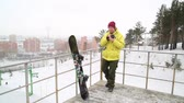 Snowboarder with SLR camera in rukhmabai in the hands