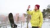 a snowboarder takes pictures on their phone, selfie Vídeos