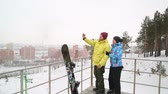 Happy couple snowboarders standing on edge of mountain peaks and taking selfie