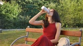 dark haired : Cute Female Teenager in Dark Red Long Dress and Eyeglasses Drinking Something from Thermo Cup Sitting on the Bench Outdoors and Showing Big Finger up.