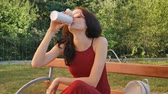 dark haired : Beautiful Dark Haired Girl in Eyeglasses Sitting on the Bench Outdoors with Beverage Bottle and Drinking Something During Warm Summer Day. Stock Footage