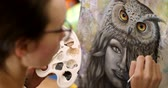 tela : Girl artist paints a picture Shaman. Artist paints picture on canvas with acrylic paints in her workshop Filmati Stock