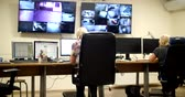 事業者 : System Security Specialist Working at System Control Center. Room is Full of Screens Displaying Various Information. 動画素材