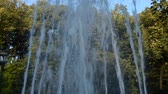 serbia : Tilt-up shot of water jets from a fountain spraying up and changing shapes in a public park of Vrnjacka Banja, Serbia. Jets stop spraying water before the end of the footage.