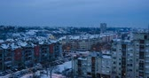 hour : Time lapse footage of a nightfall in a city in winter, with roofs and streets, partly covered with snow Stock Footage