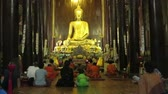 motosiklet : People praying and squatting in front of a golden Buddha statue - steady camera medium shot Stok Video