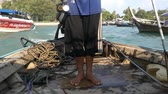 Sailor standing bare feet on wooden long-tail boat using a long iron  -  fixed camera closeup view Stockvideo