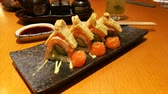 Beautiful decorated sushi dish served on a black plate -  fixed camera closeup view Stockvideo