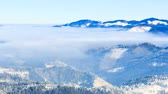 mysterious : Winter Landscape. Fog moving over the mountain in winter with a blue sky