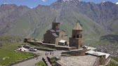 コー​​カサス : Aerial view of the Holy Trinity Church and the Holy Trinity Church, under Mount Kazbegi, Georgia 動画素材