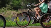desfrutar : Girl in a dress on a bicycle among people, wheels focus in in summer evening.