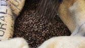 carry out : Process pour out of fried coffee grains into bag in factory.