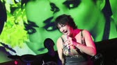 Lolita Milyavskaya perform on stage with plush hare on hand in nightclub. Stok Video