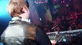 Back side of Dj in leather jaket at turntable in crowded nightclub. Headphones