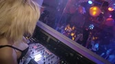 Back side of blonde Dj girl dance at turntable. Club. Slow motion. People
