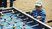 Little boy in cap absorbedly play american table soccer with adult. Sand. People