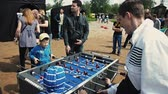 Little boys in cap play american table soccer with adult. Sand. Summer festival Stok Video
