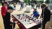 Four boys in cap absorbedly play american table soccer. Sand. Festival. People
