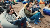 Many people lie on big beanbags on sand. Summer festival. Sunny day. Audience Stok Video