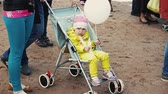 Little girl in yellow suit hold balloon sit in pram. Summer festival. People Stok Video