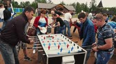 Three adult men absorbedly play american table soccer. Summer festival. Sunny