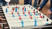 Faces of three adult men absorbedly play american table soccer. Summer festival Stok Video