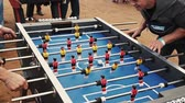 Four adult men absorbedly play american table soccer. Breathe on ball. Festival Stok Video